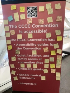 "The original CCCC sign, a red sign with white letters, that reads: ""The CCCC Convention is accessible! The CCCC Convention has accessibility guides for the Convention; Quiet, lactation, and family rooms at convention sites; Childcare grants; Gender-neutral bathrooms; Interpreters"" has dozens of sticky notes with messages written on them."