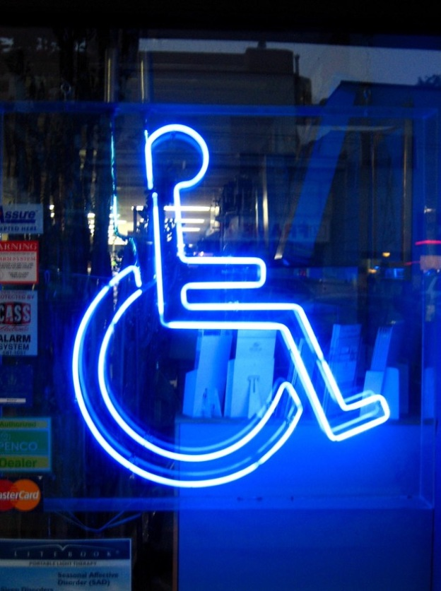 Universal sign for access of person in wheelchair created in blue neon in a window.