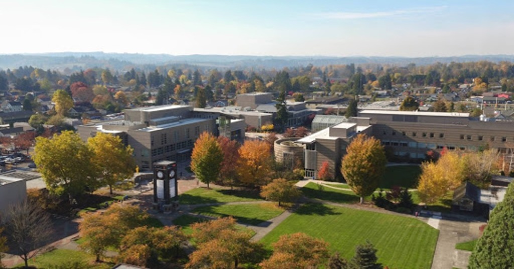 An aerial image of Centralia College's main campus. Several buildings are clustered around a bright green lawn with a clock tower and trees whose orange and red leaves mark the early autumn season.