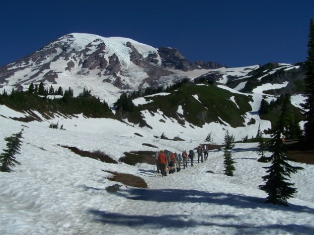 A snowy Mt. Ranier rises in the background with a group of climbers starting up across the high meadows.