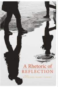 The book cover of A Rhetoric of Reflection, edited by Kathleen Blake Yancey, featuring a black and white picture of a person examining their reflection in a puddle on the ground.