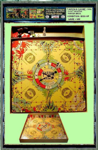 An aerial image of the Tarzan game board. It features a spinner in the center of a yellow board with red and green images of leaves around the edges.
